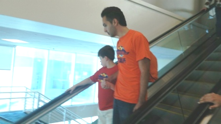 Staff with child going down escalator